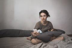 La giovane madre allatta al seno il bambino e lo smartphone, stile di vita, Fotografie Stock Libere da Diritti