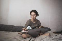 La giovane madre allatta al seno il bambino e lo smartphone, stile di vita, Fotografie Stock