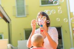La giovane madre allegra che sta all'aperto soffiante bolle per lei Fotografie Stock