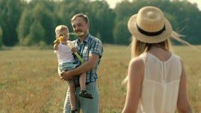 La giovane madre attraente gira a partire dalla macchina fotografica per sembrare come la sua famiglia gioca con le bolle di sapo stock footage