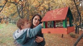 La giovane madre che tiene il suo piccolo figlio sveglio, il ragazzo mette l'alimento nell'alimentatore dell'uccello in un parco  stock footage