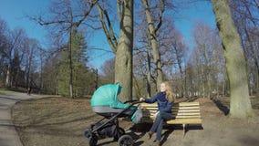 La giovane madre con il bambino in carrozzino si siede sul banco in parco 4K stock footage