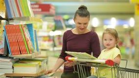 La giovane madre con sua figlia sceglie i libri in supermercato Bella figlia che si siede in un carretto del supermercato e stock footage