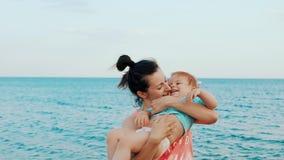 La giovane madre con la sua piccola neonata si diverte su una spiaggia nel giorno di estate archivi video