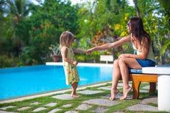 La giovane madre e la sua piccola figlia giocano vicino al Fotografia Stock