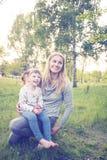 La giovane madre e la sua piccola figlia stanno godendo della vita in parco fotografie stock libere da diritti