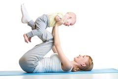 La giovane madre fa gli esercizi di forma fisica insieme al neonato isolato Fotografie Stock
