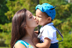 La giovane madre felice bacia il suo piccolo figlio Immagine Stock