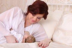 La giovane madre felice che si trova a letto ed allatta il bambino Fotografia Stock