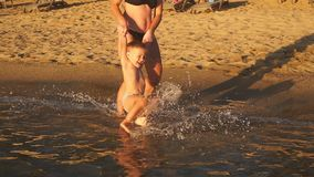 La giovane madre felice gioca con suo figlio in mare che sorride e che ride stock footage