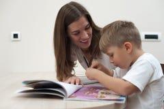 La giovane madre felice sta studiando con il suo giovane figlio Immagine Stock