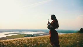 La giovane madre gioca con il bambino in un campo del weat sui precedenti del lago video d archivio
