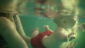 La giovane madre insegna al suo neonato sveglio a tuffarsi lo stagno Il bambino ? deliziato Lo sviluppo dei bambini, paternità stock footage