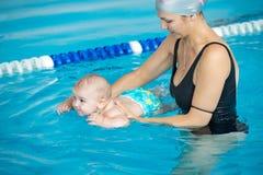 La giovane madre insegna al suo piccolo figlio, come nuotare in una cacca di nuoto fotografia stock libera da diritti