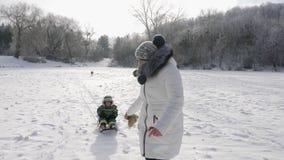 La giovane madre rotola suo figlio sullo sledding stock footage