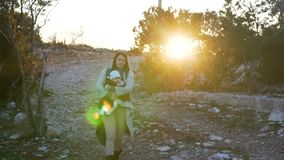 La giovane madre tiene il neonato nelle sue armi che cammina su una traccia di escursione archivi video