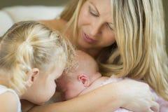 La giovane madre tiene la ragazza di neonato con la giovane sorella Immagini Stock Libere da Diritti