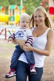 La giovane madre tiene sulle mani di suo figlio di due anni Fotografia Stock Libera da Diritti