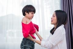 La giovane mamma asiatica si ? agghindata il figlio che le attrezzature per la preparazione vanno a scuola Concetto del figlio e  fotografia stock libera da diritti