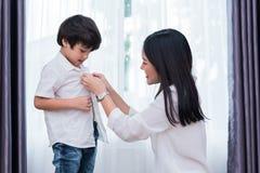 La giovane mamma asiatica si ? agghindata il figlio che le attrezzature per la preparazione vanno a scuola Concetto del figlio e  fotografia stock