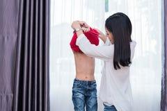 La giovane mamma asiatica si ? agghindata il figlio che le attrezzature per la preparazione vanno a scuola Concetto del figlio e  immagine stock
