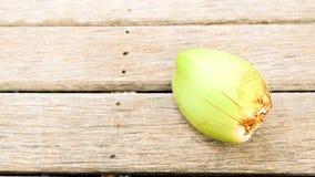 La giovane noce di cocco verde fresca ha mostrato su fondo di legno marrone Fotografie Stock