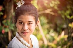 La giovane orchidea asiatica felice della tenuta della donna con un sorriso felice dentro graden fotografia stock