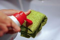 La giovane padrona usa il pulitore liquido del lavandino senza guanti immagine stock