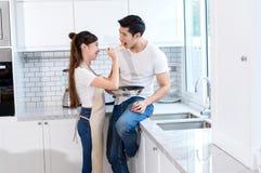 La giovane pentola asiatica della tenuta della ragazza con gli spaghetti dà l'alimentatore a cucchiaiate alle coppie del giovane immagini stock