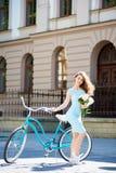 La giovane posa femminile attraente con le peonie si avvicina alla bici d'annata blu davanti a buiding storico nel centro urbano fotografia stock libera da diritti