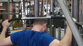 La giovane prova atletica dell'uomo esegue gli esercizi del muscolo dorsale sulla macchina di esercizio della barra di pulldown i stock footage