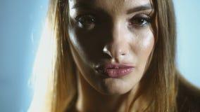 La giovane ragazza affascinante con un trucco delicato apre gli occhi ed esamina la macchina fotografica stock footage