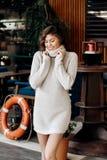 La giovane ragazza affascinante vestita nel beige tricotta le pose del vestito nella via immagine stock libera da diritti