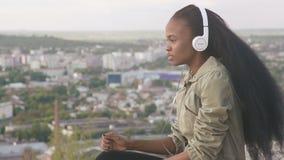 La giovane ragazza afroamericana adorabile ascolta musica e sorridere Bella ragazza nera all'aperto sul fondo di paesaggio urbano stock footage