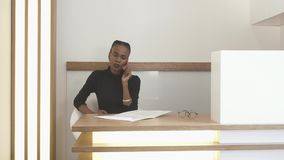 La giovane ragazza afroamericana alla ricezione sta parlando tramite telefono cellulare e sta riempiendo qualcosa nella forma uff archivi video