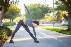 La giovane ragazza afroamericana nell'allenamento copre l'allungamento su una b Fotografie Stock