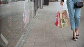 La giovane ragazza alla moda cammina intorno alla città con i pacchetti a disposizione stock footage