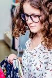 La giovane ragazza alla moda sceglie i vestiti nel boutique Comperando una f immagine stock