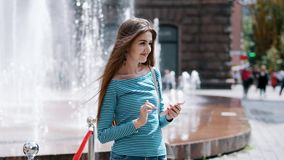 La giovane, ragazza alla moda utilizza uno smartphone su una via della città, una donna stampa un messaggio, chating video d archivio