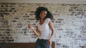La giovane ragazza allegra afroamericana riccia si diverte il dancing sul letto a casa archivi video