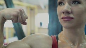 La giovane ragazza atletica che mostra i muscoli, assistente spruzza l'acqua lei dalla pistola a spruzzo archivi video