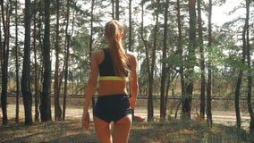 La giovane ragazza atletica esile in pantaloncini corti con le natiche sexy cammina attraverso il legno video d archivio