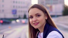 La giovane ragazza attraente, gira per esaminare la macchina fotografica, sorridente Anche tempo, fondo del centro e vago archivi video