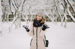 La giovane ragazza attraente in vetri del nerd, piumino beige e cappello tricottato con un fiocchetto sorride ed imbroglia intorn fotografia stock