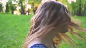La giovane ragazza attraente volteggia i capelli nel primo piano del parco Movimento lento archivi video