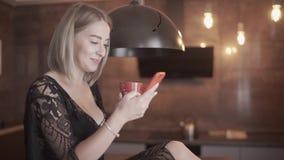 La giovane ragazza bionda felice che per mezzo dello smartphone comunica con il ragazzo che si siede sulla tavola archivi video