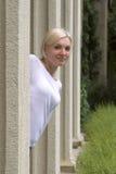 La giovane ragazza bionda osserva fuori da dietro una colonna Fotografia Stock