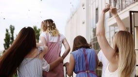 La giovane, ragazza bionda sbalorditiva è spruzza i coriandoli fuori dal balcone Esigendo per le sue amiche ognuno stock footage