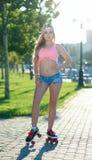 La giovane ragazza bionda sexy che pattina sui rulli d'annata si scola la via Fotografia Stock Libera da Diritti