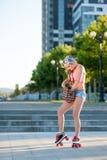La giovane ragazza bionda sexy che pattina sui rulli d'annata si scola la via Fotografie Stock